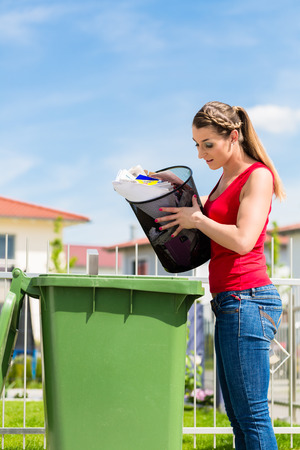 waste basket: Woman throwing waste paper away in container