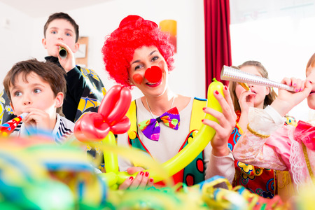 clown birthday: Children celebrating birthday party with noisemakers while a clown is visiting entertaining the kids