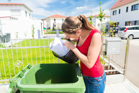 thrash: Woman throwing waste paper away in container