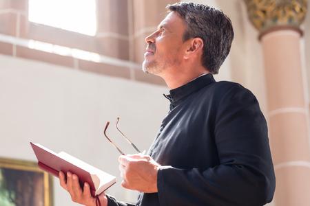 Prêtre catholique lecture de la Bible à l'église Banque d'images