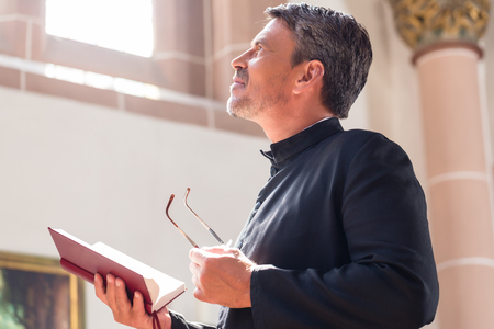 the church: Sacerdote católico que lee la biblia en la iglesia