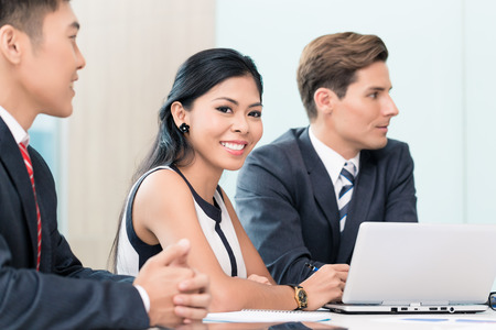 international business: Asian Business woman in meeting looking at camera Stock Photo