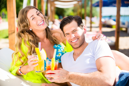 lake beach: Woman and man with drinks in beach bar on lake
