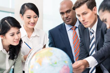 inteligencia: Gente de negocios en reunión de estrategia en discusiones sobre nuevos mercados miran un globo