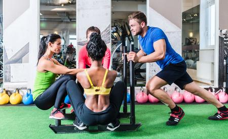 Man duwen vrouwen op de kar als fitness oefening in de sportschool