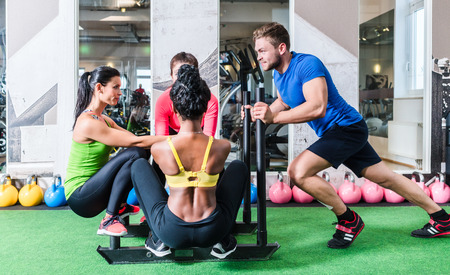Man pushing women on cart as fitness exercise in gym