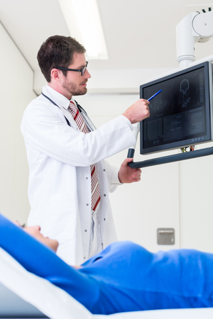 tomograph: Doctor explaining patient MRI scan on screen Stock Photo
