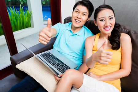 house wife: Asian woman and man surfing showing thumbs up in their living room at home