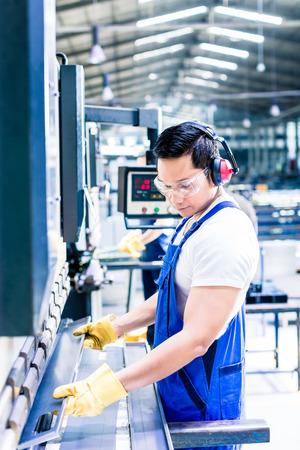 work worker: Asian worker in factory at metal skip machine putting work piece in
