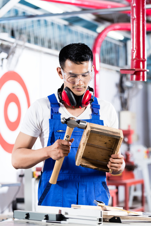 cabinet maker: Asian Carpenter in wood workshop working on a box measuring the piece with a rule