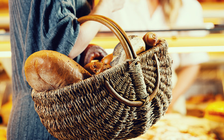 salesgirl: Customer shopping bread in baker carrying basket, filtered image