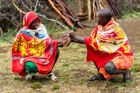 concluding: Massai men shaking hand concluding an agreement