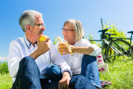 Ältere Paare, Obst essen und trinken am Picknick im Sommer, schöne Landschaft im Hintergrund
