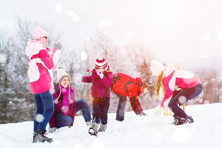 pelea: Familia que juega en la nieve que tiene pelea con bolas de nieve
