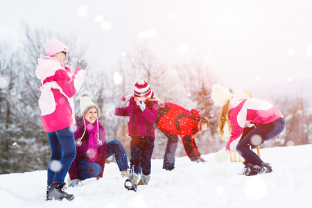 snowball: Family playing in snow having fight with snowballs Stock Photo