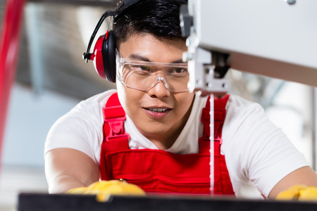 cabinet maker: Chinese worker on saw in industrial factory cutting a work piece