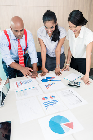 strategy meeting: Asian business team in strategy meeting bowing on desk over with graphs and numbers Stock Photo