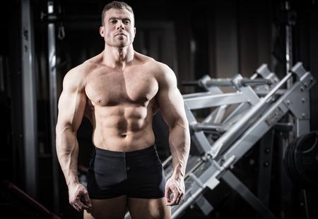 musculoso: Hombre fuerte haciendo musculación en el gimnasio de pie delante de un juego de mancuernas Foto de archivo
