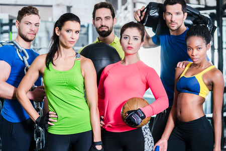 men and women: Group of women and men in gym posing at fitness training standing together with gear and dumbbells