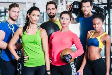 grupo de hombres: Grupo de mujeres y hombres en el gimnasio que presentan en el entrenamiento de la aptitud que se unen con el equipo y pesas