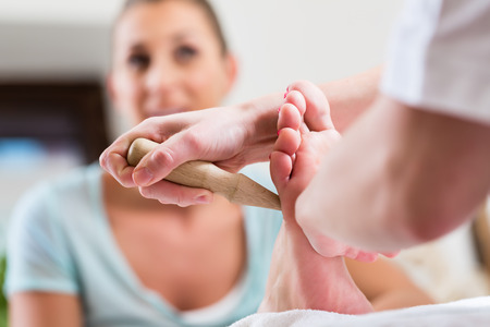 Women at reflexology having foot massaged or pressed with wooden stick