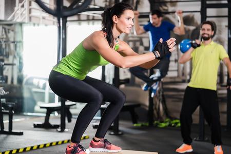 gente saltando: Grupo de hombres y mujeres en el gimnasio de entrenamiento funcional que realizan ejercicio físico