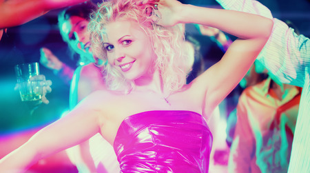 dancefloor: Girl dancing in disco club celebrating with friends, filtered image