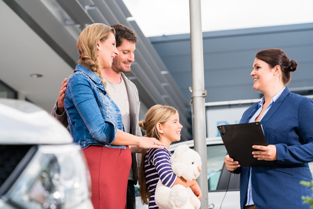 selling service: Car dealer advising family on buying auto showing price list Stock Photo