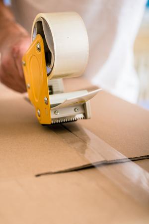 packing tape: Man taping packing case