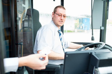 drivers seat: Bus driver selling tickets in bus from drivers seat