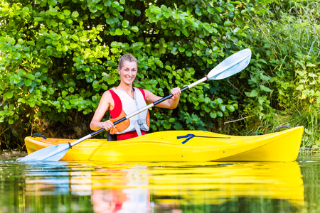 jacked: Woman driving with kayak on forest river