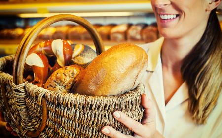 saleslady: Baker woman in backer selling bread in basket, filtered image Stock Photo