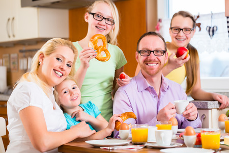 family together: Family having joint breakfast in kitchen eating and drinking Stock Photo