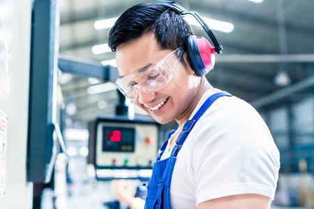 Asian machine operator in production plant checking data Foto de archivo