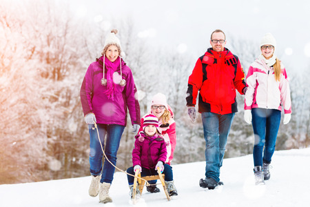 walk in: Family having winter walk in snow with sled