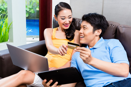 house shopping: Asian couple shopping online in internet with laptop and credit card