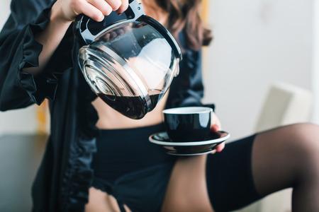 Woman in dressing gown having coffee for breakfast