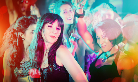 dancefloor: Crowd dancing in club having party, filtered image