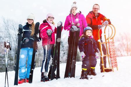 Famille avec traîneau et ski en faisant des sports d'hiver