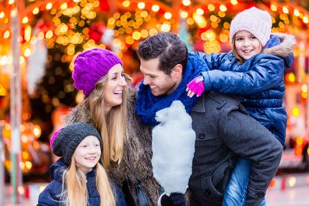 Famille coton manger des bonbons sur le marché de Noël Banque d'images