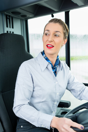 drivers seat: Female bus driver in drivers seat