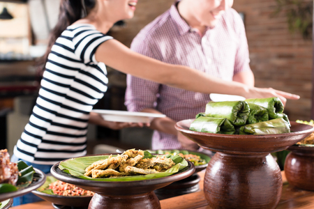 catering food: Asian woman and man choosing food at Indonesian buffet in restaurant
