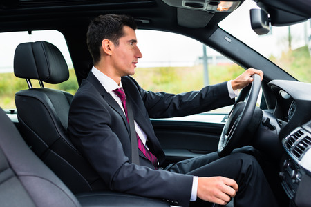 Man driving his car for business travel wearing a suit Reklamní fotografie