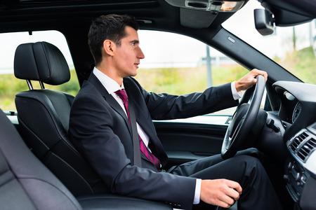 Man rijden zijn auto voor zakelijke reizen dragen van een pak Stockfoto