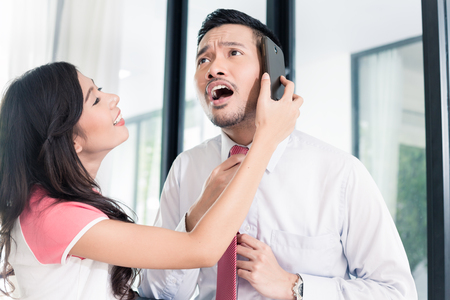 trabajando en casa: El hombre ya se usa el teléfono para los negocios de salir de casa, su esposa es vinculante su corbata como ya es tarde para la oficina