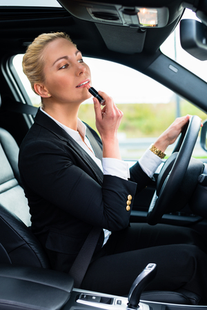 driving a car: Woman using lipstick while driving her car