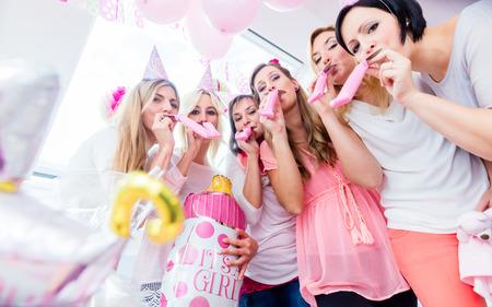 Gruppe von Frauen auf Baby Shower Party, die Spaß tragen Partei Hüte weht Papier Streamer