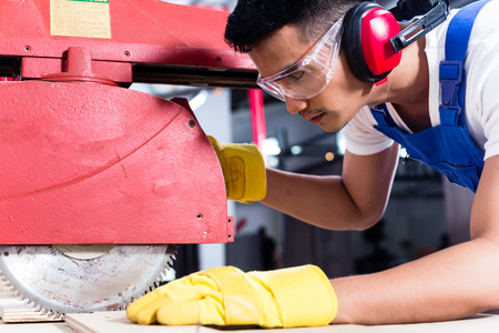 safety goggles: Carpenter in Asian workshop with circular saw in a manufacturing factory Stock Photo