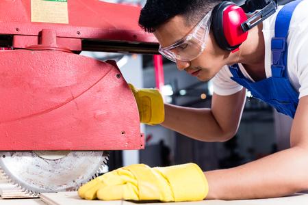 Carpenter in officina asiatico con sega circolare in una fabbrica di produzione