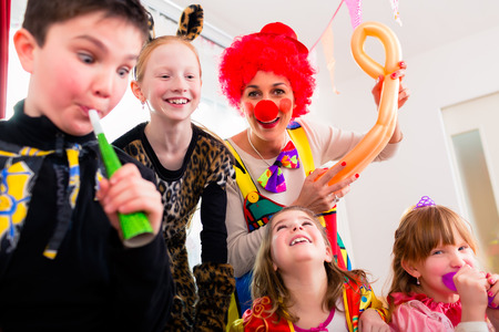 noise: Children celebrating birthday party with noisemakers while a clown is visiting entertaining the kids